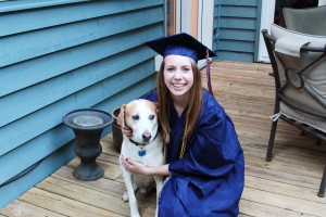 Girl in a graduation gown with her dog