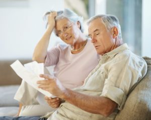 Elderly man with his wife going through documents on couch , worried about savings