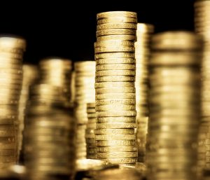 Tall stacks of UK pound coins against a dark background.